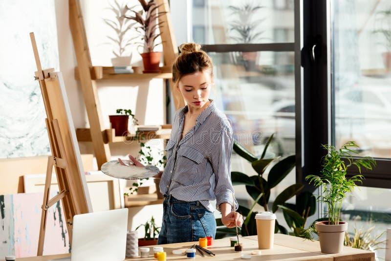 artiste féminin tenant la palette et mettant la brosse dans la peinture photo stock