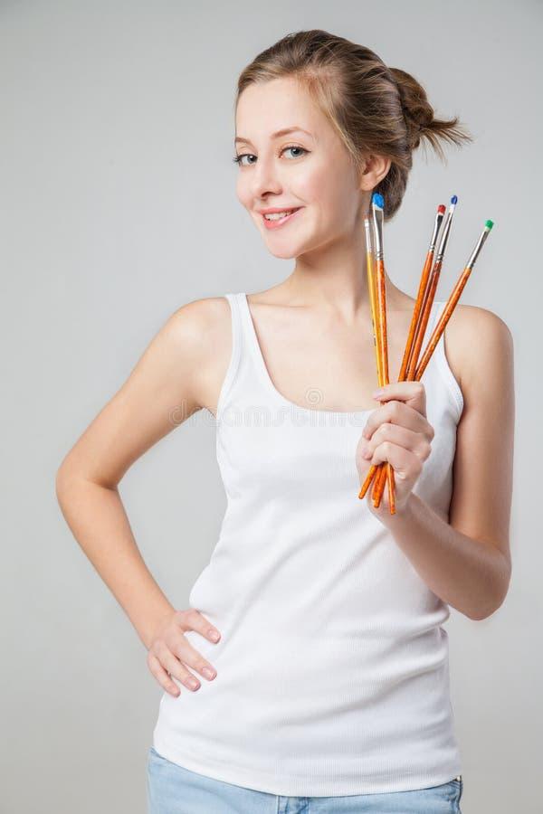 Artiste-fille de sourire avec le groupe de pinceaux image libre de droits