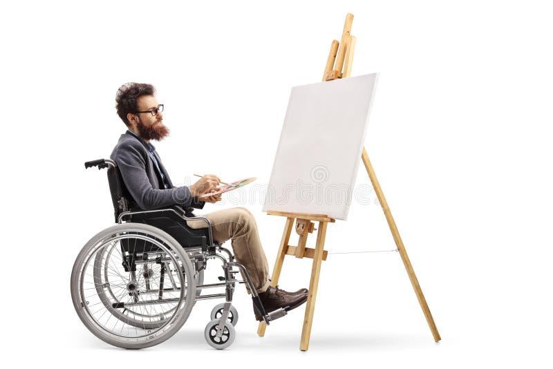 Artiste masculin handicapé dans une peinture de fauteuil roulant sur une toile photos stock