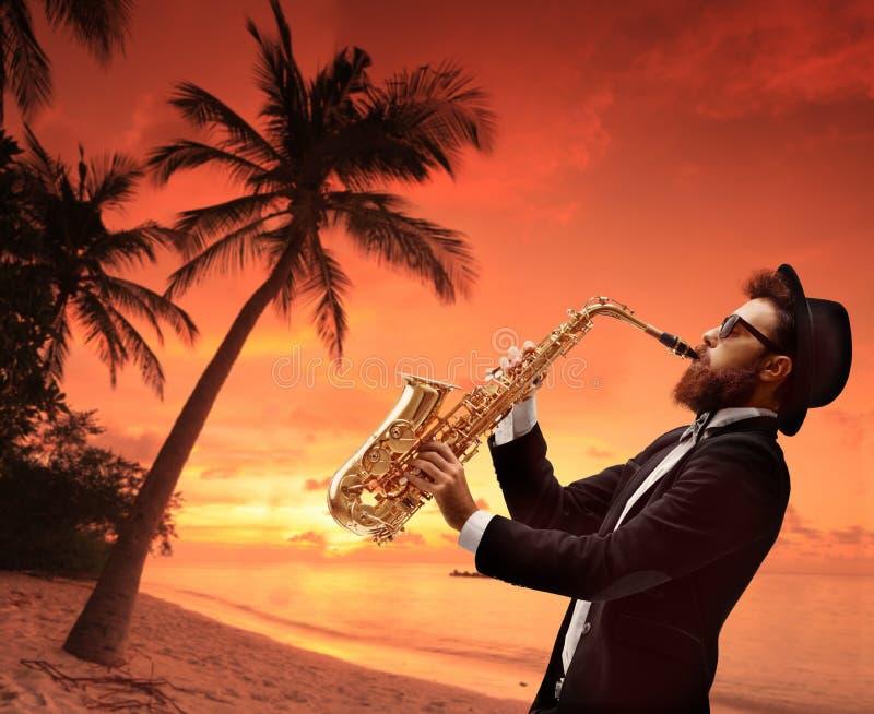 Artiste masculin jouant du saxophone avec plage et palmier au coucher du soleil photos libres de droits