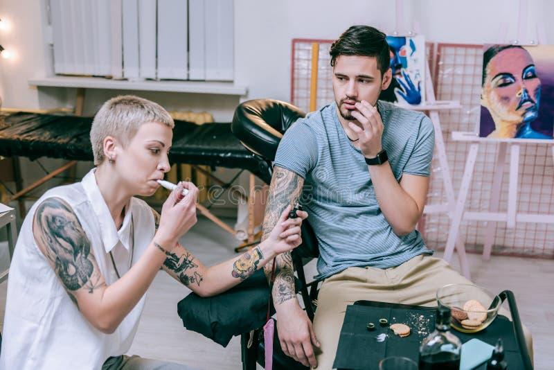 Artiste multifonctionnel de tatouage travaillant avec le tatouage et la cigarette électronique de tabagisme photographie stock