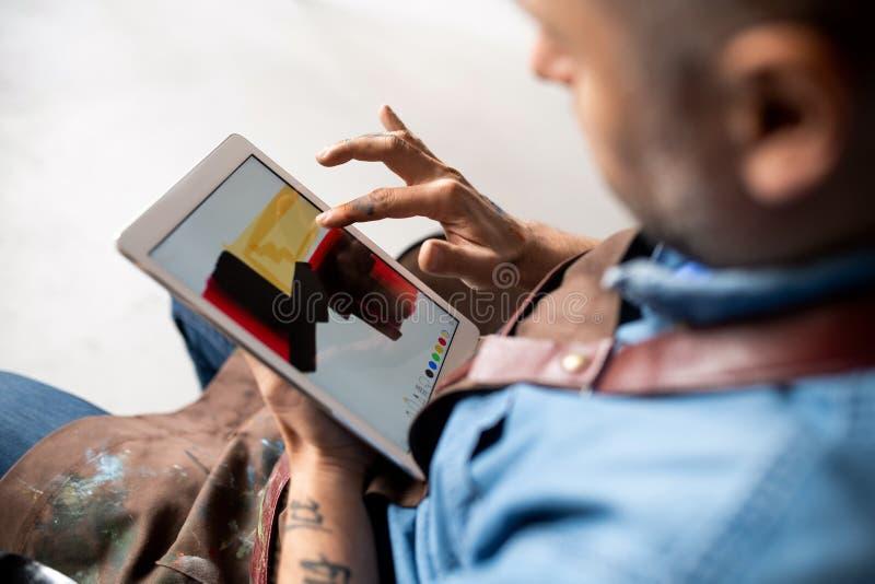 Artiste professionnel en tenue de travail utilisant un nouveau programme de peinture dans le pavé tactile images libres de droits