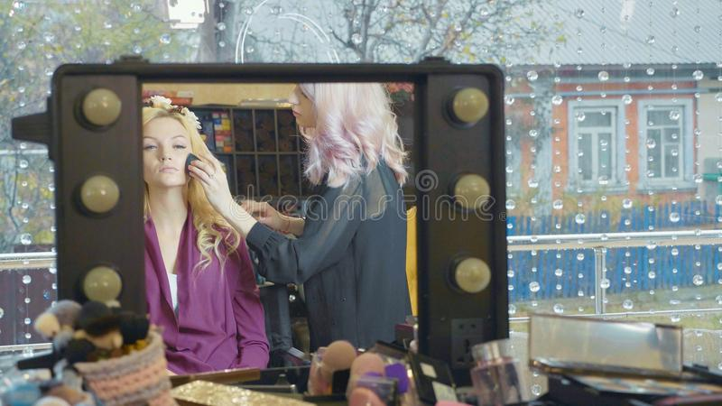 Artiste professionnel faisant à maquillage la jeune jolie femme d'affaires image stock