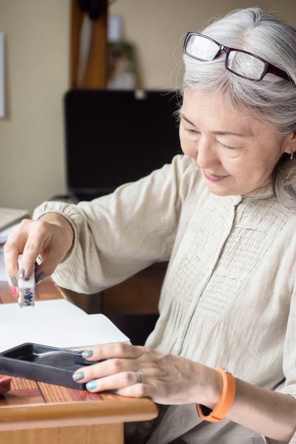 Artiste supérieur asiatique de femme employant Suiteki et sudzuri photos libres de droits