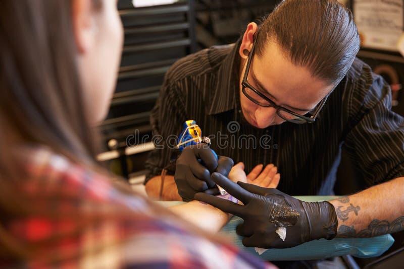 Artiste Working On Design de tatouage pour le client féminin photo stock