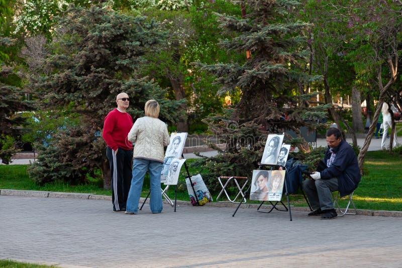 Artisti con le immagini della gente ai cavalletti nell'offerta del parco della città per estrarre un ritratto ai passanti un chia immagine stock