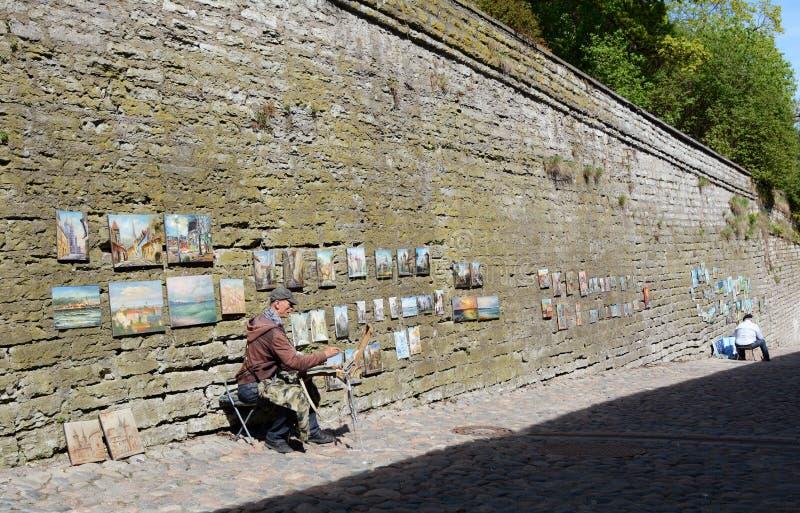 Artisti della via che dipingono sulla via lunga della gamba, Tallinn, Estonia immagini stock