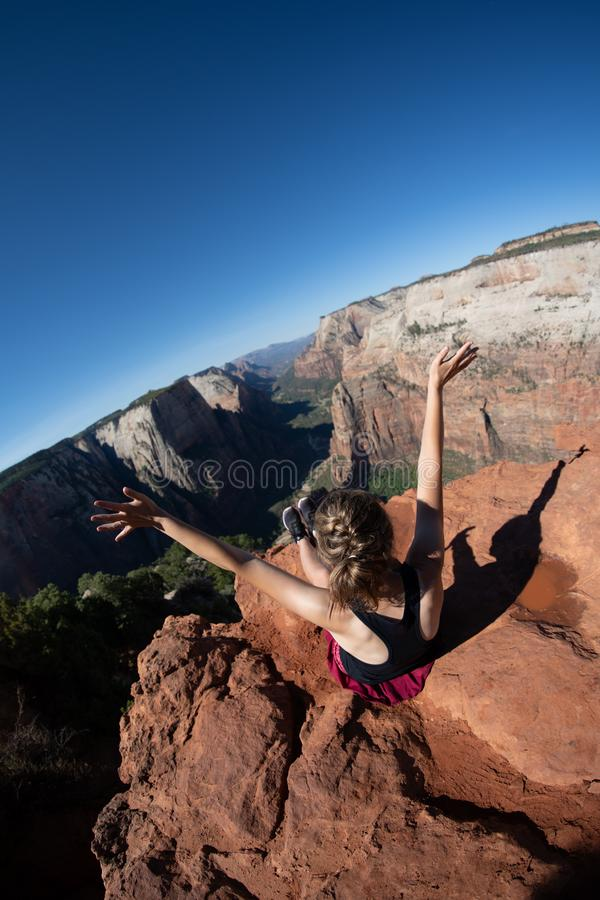 Artistic angle of a woman sitting on the top of Observation Point in Zion National Park with arms raised. Concept for. Accomplishment and achievement royalty free stock image
