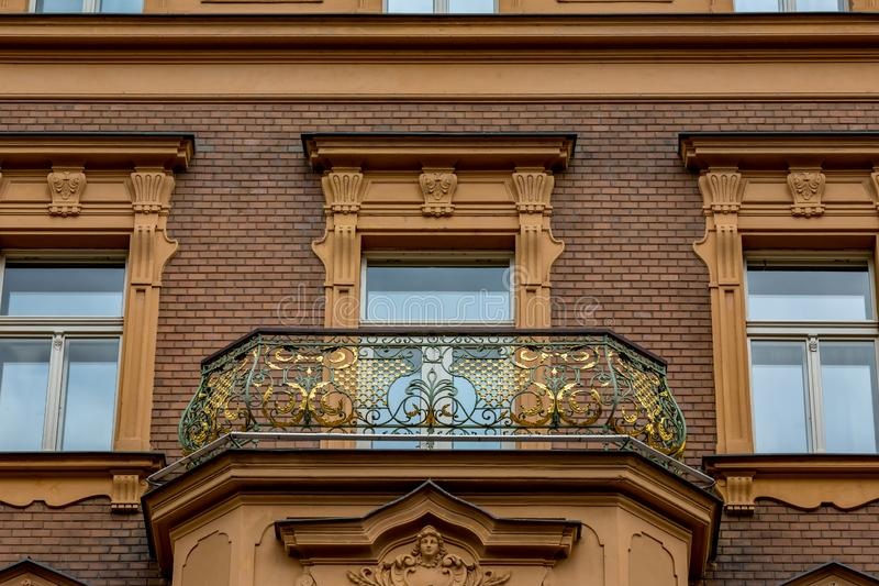 Artistic architectural details of building, Prague. Amazing artistic architectural details of a residential building with gilded decorated balcony in the old royalty free stock image