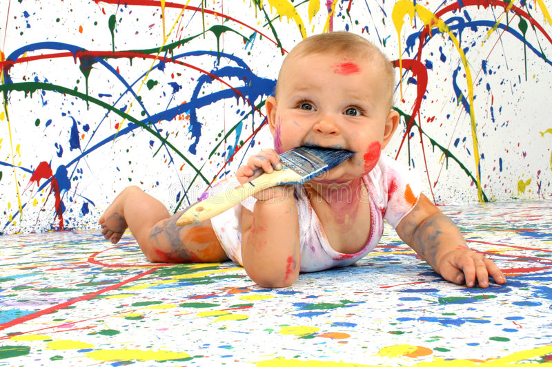 Artistic Baby. Beautiful baby covered in bright paint with paint brush stock images