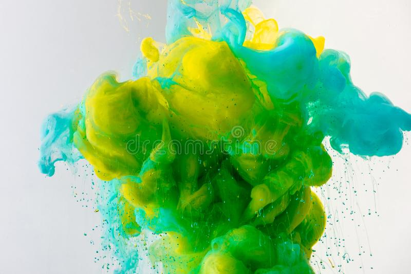 Artistic background with flowing turquoise, yellow and green paint in water, isolated on grey royalty free stock images