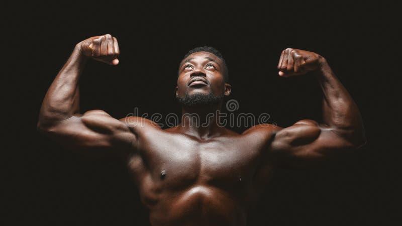 Artistic black athlete flexing biceps over black background. Artistic african athlete flexing biceps over black studio background, looking up stock photo