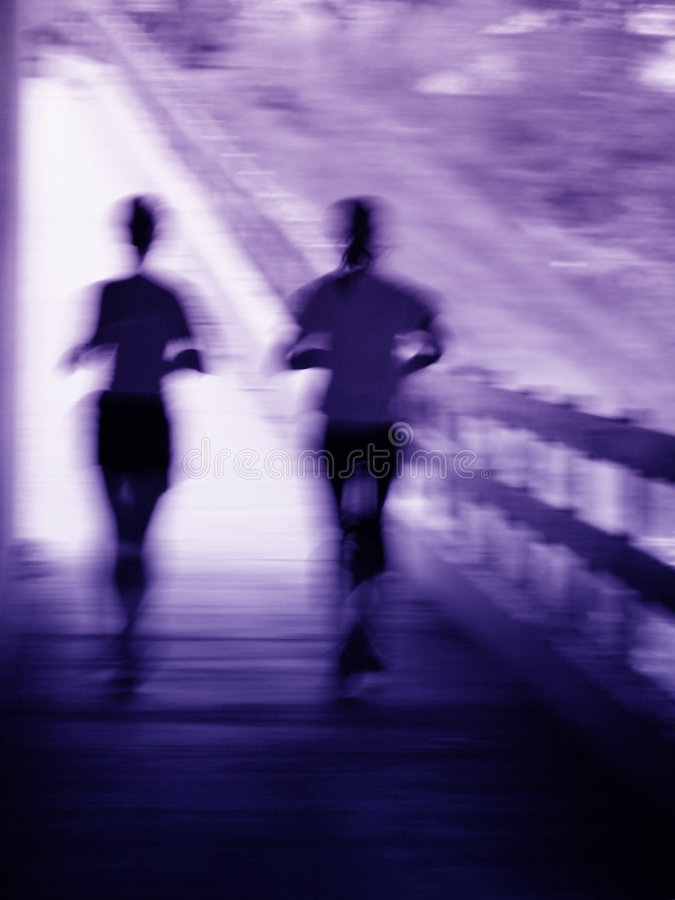 Artistic blur of a running couple. Artistic blue and purple blur of a running couple royalty free stock photo