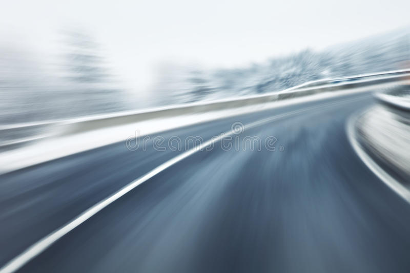Artistic blurry fast winter driving. Artistic blurry dangerous fast driving at the icy snow road. Motion blur visualizies the speed and dynamics royalty free stock images