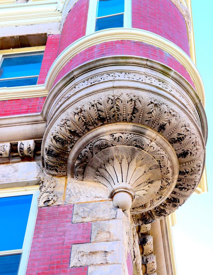 Artistic Building Corner With Intricate Design. A masterpiece of architectural work, this historic building shining brightly in pink with gold or beige inset stock image