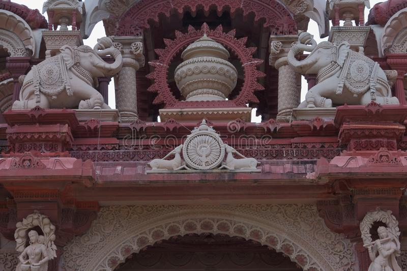 Artistic carving on red and white stone of main gate, bheru tarak dham, rajasthan, I ndia. Vase, ornamental elephants, dancers, deer and others artistic carving stock photography