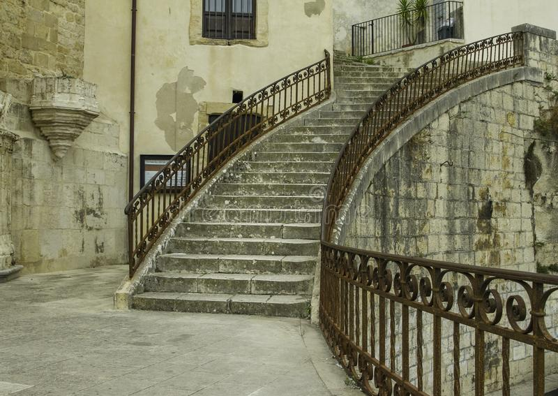 Artistic circular steps with antique decorated metal handrail in old Ragusa Ibla in Sicily. Artistic circular steps with antique decorated metal handrail among royalty free stock photo