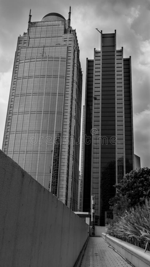 An Artistic Cloudy skies over the skyscraper towers. Symmetrical photograph on an artistic cloudy skies over the skyscraper tower at Jakarta city in a black and royalty free stock photos