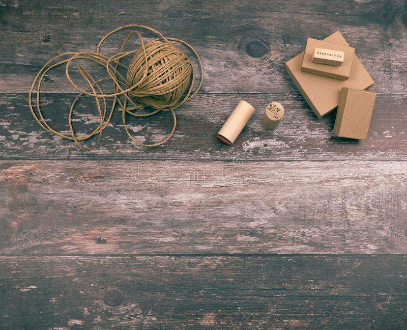 Artistic crafting supplies and art tools of hemp yarn, natural cardboard boxes and stamps for creative homemade gift. Wrapping and handmade crafts, on wood stock photo
