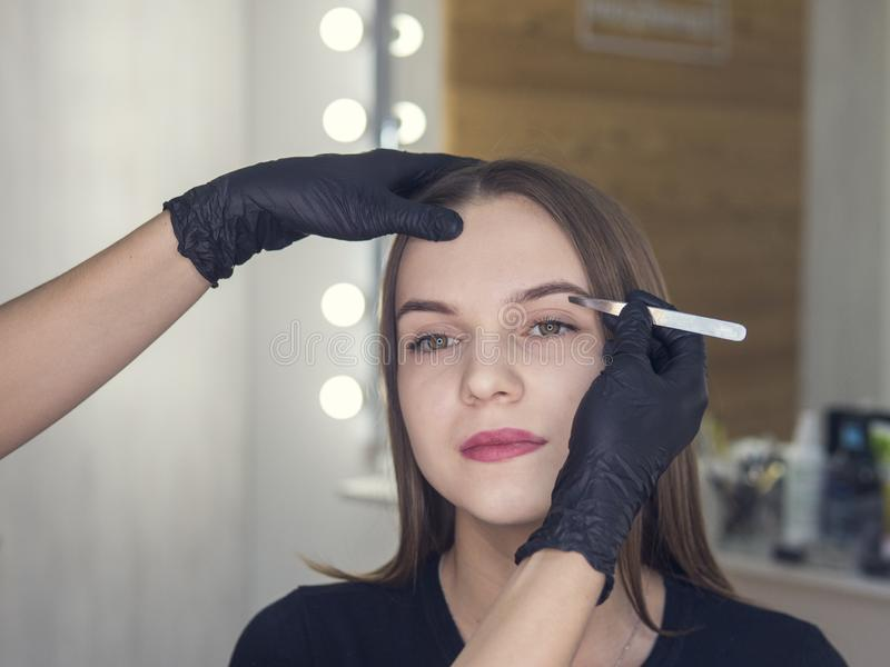 Artistic design of eyebrows. Correction. Pin forceps. Woman having her eye brows tinted. Semi-permanent makeup for eyebrows. Focus royalty free stock images