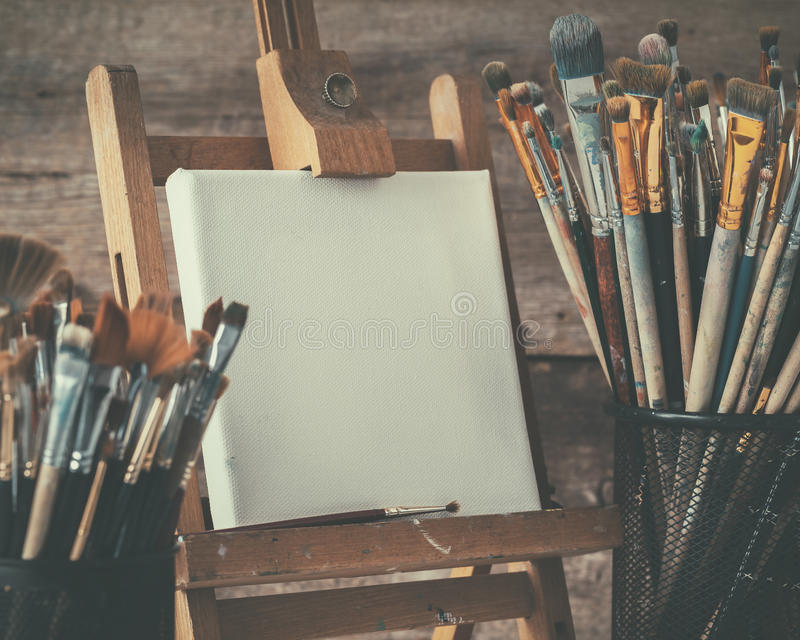 Artistic equipment: artist canvas on easel and paint brushes. stock image