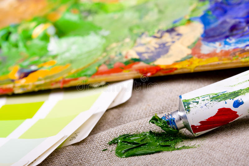Artistic equipment and color chart. Artistic equipment: paint, brushes and knives on paint background stock photography
