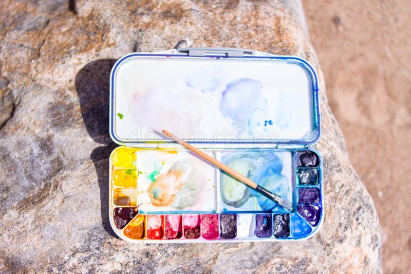 Artistic equipment: paint brushes, palette and paintings on rock in nature at sunny summer day - creation, drawing and freedom con stock photo