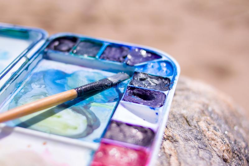 Artistic equipment: paint brushes, palette and paintings on rock in nature at sunny summer day - creation, drawing and freedom con stock image