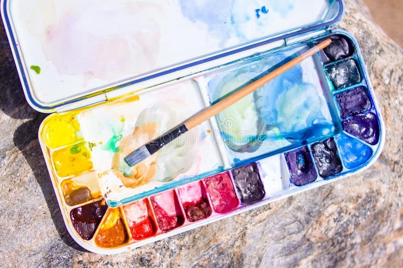 Artistic equipment: paint brushes, palette and paintings on rock in nature at sunny summer day - creation, drawing and freedom con. Creation, drawing and freedom stock images