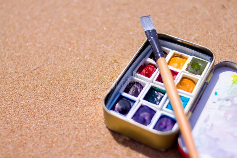 Artistic equipment: paint brushes, watercolors paintings on sand background at sunny summer day - creation, drawing and freedom co. Creation, drawing and freedom stock images