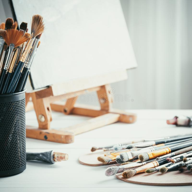 Artistic equipment in painter studio: easel, paint brushes, tubes of paint, palette and paintings on work table. royalty free stock photography