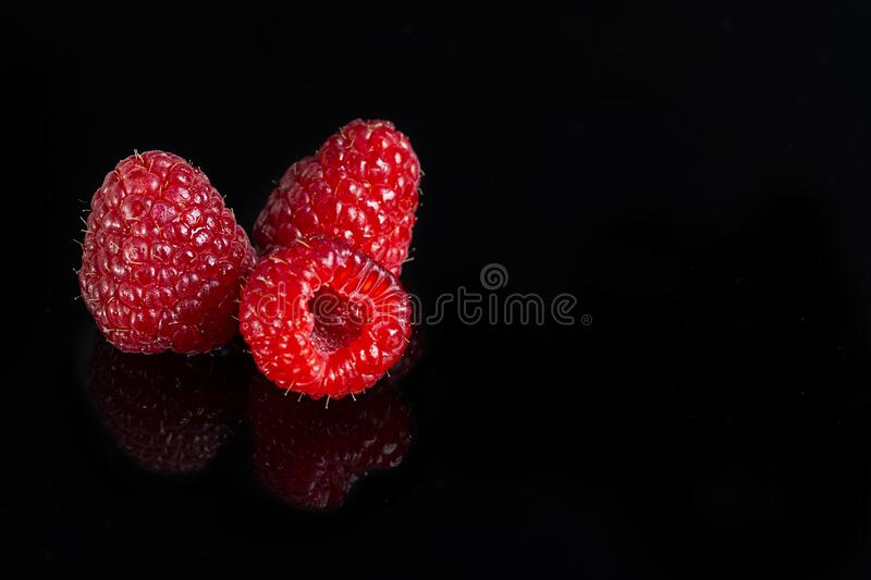 Artistic fresh raspberries reflection on a black reflective surface. Raspberry with black background.  stock image