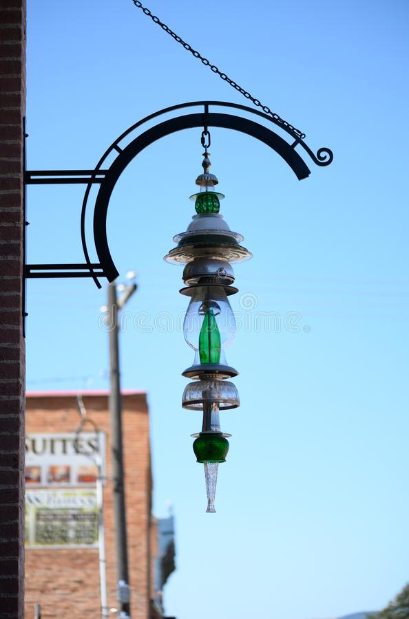 Artistic glass light fixture hanging from iron semicircle. Artistic light fixture hanging outside a shop on a sunny day in Philipsburg Montana stock images