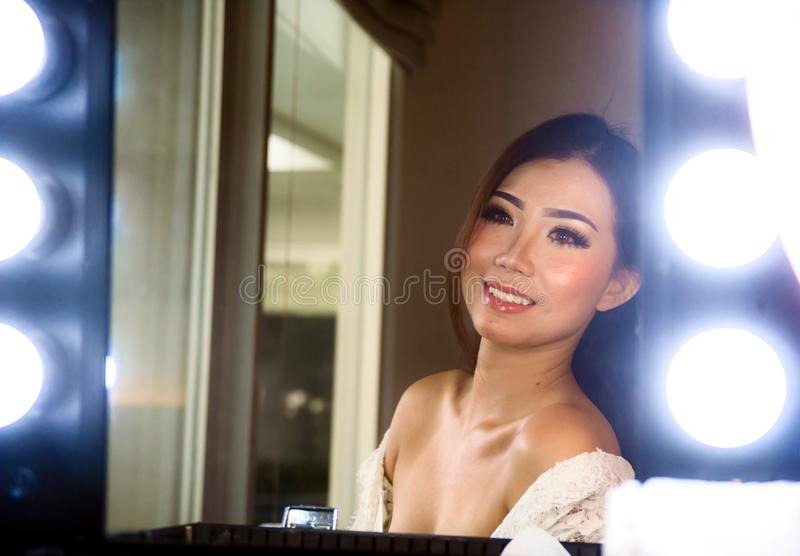 Artistic glossy portrait of young beautiful and gorgeous Asian C. Hinese woman at make up beauty room looking happy smiling reflection on the mirror in style royalty free stock image