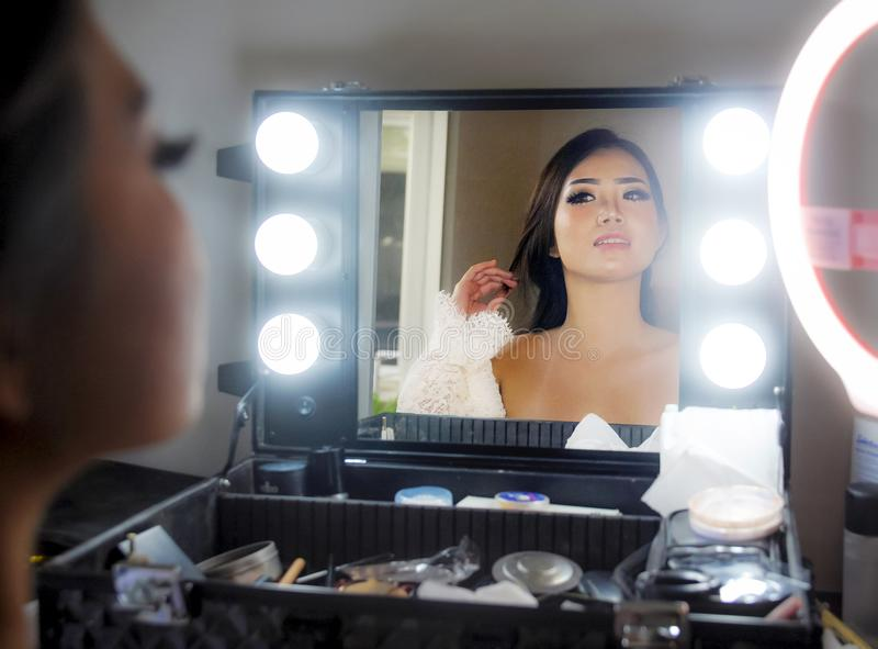 Artistic glossy portrait of young beautiful and gorgeous Asian Chinese woman at make up beauty room looking happy. Admiring reflection on the mirror in style royalty free stock photo