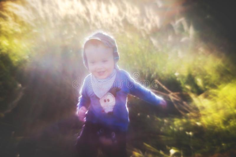 Artistic look portrait of a child in nature. Interesting bokeh of manual lens. Boy in nature fields, sun shine stock photo