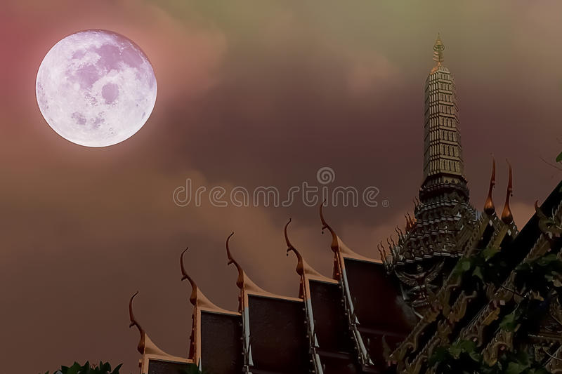Artistic Nighttime Photo of Thai Temple and Full moon and dramatic sky and clouds. stock photography