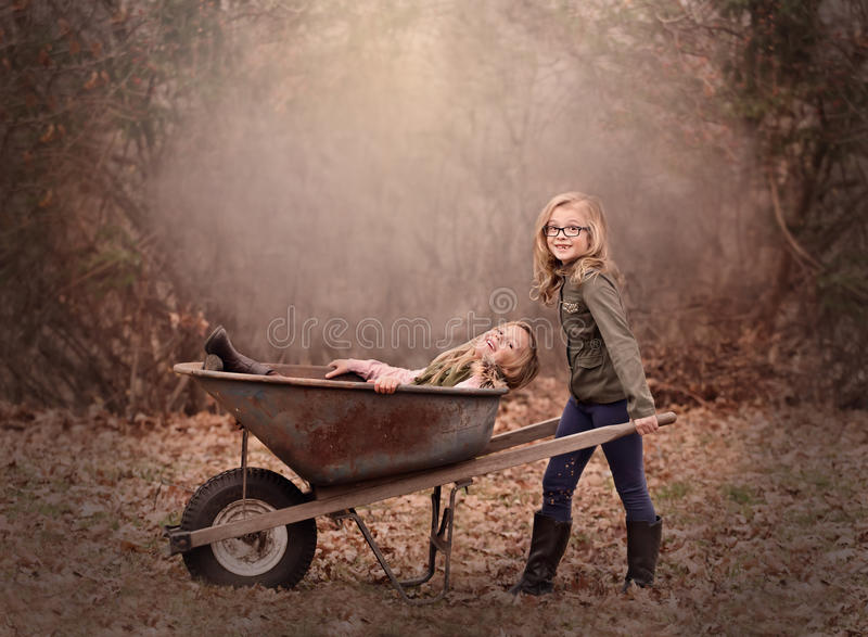 Artistic outdoor portrait of two blond girls playing with a wheel barrow in a woods. Artistic moody outdoor portrait of two blond girls playing with a wheel stock photos
