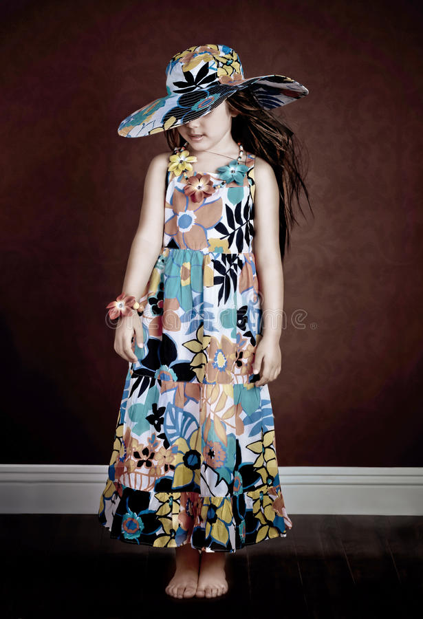 Artistic portrait. Girl with spring dress and matching hat and necklace royalty free stock images