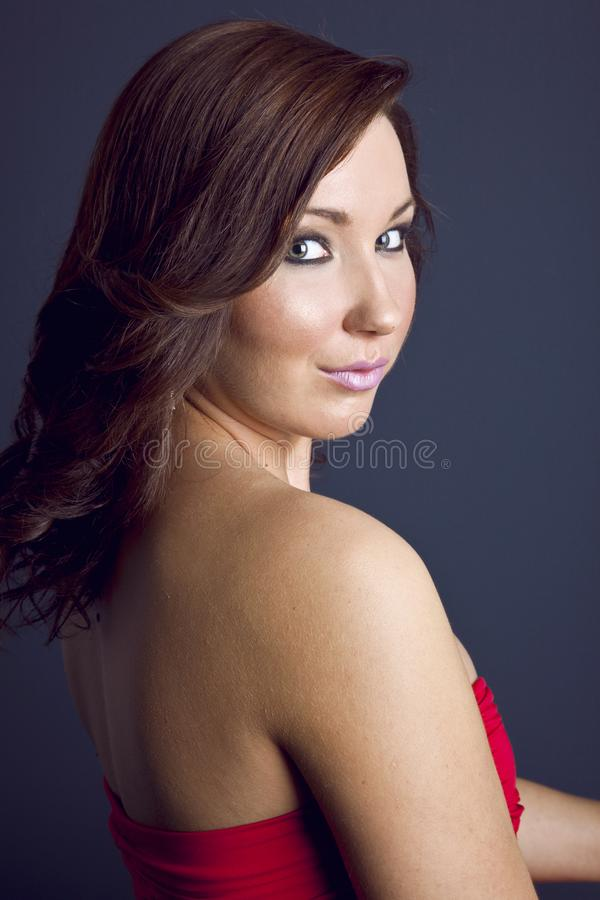 A Beautiful, Happy, Young, Smiling woman looking over her shoulder. Portrait - Fashion and beauty shot. Catseye makeup, hairstyle. stock photos