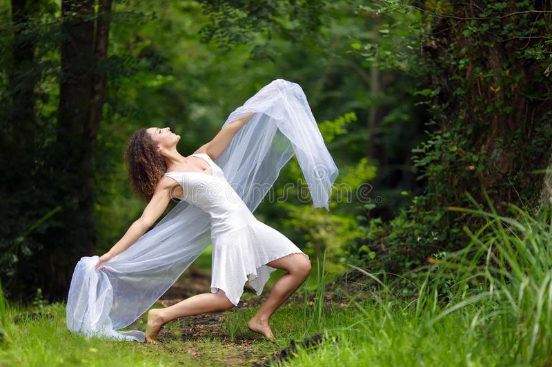 Artistic portrait of a beautiful. Barefoot woman in a stylish white dress striking a dramatic pose against a forest backdrop of lush green trees royalty free stock photo