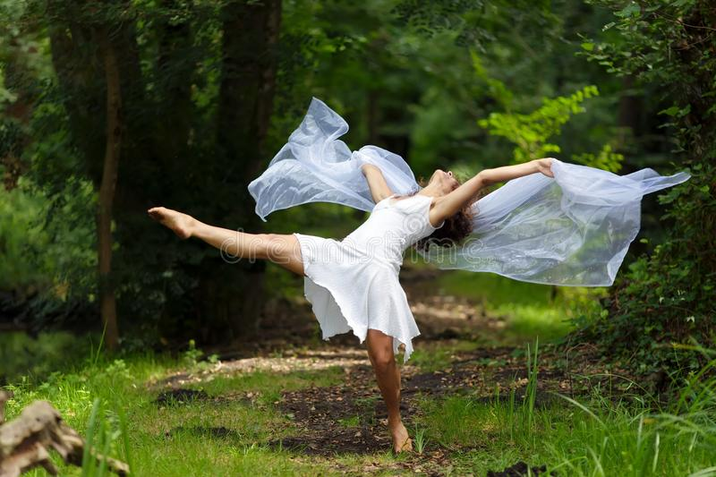 Artistic portrait of a beautiful. Barefoot woman in a stylish white dress striking a dramatic pose against a forest backdrop of lush green trees stock image