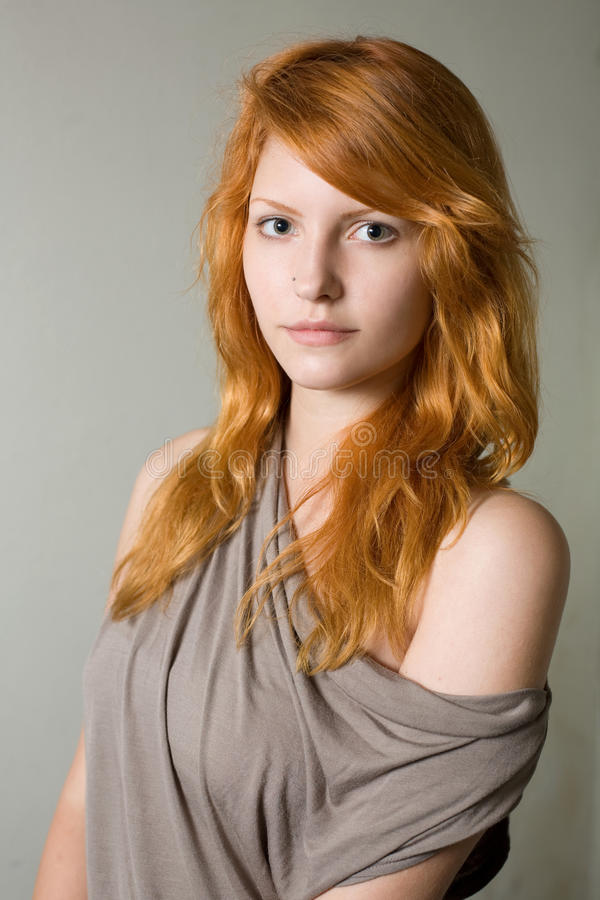 Artistic portrait of gorgeous young redhead. Artistic portrait of gorgeous young redhead wearing gray top stock images