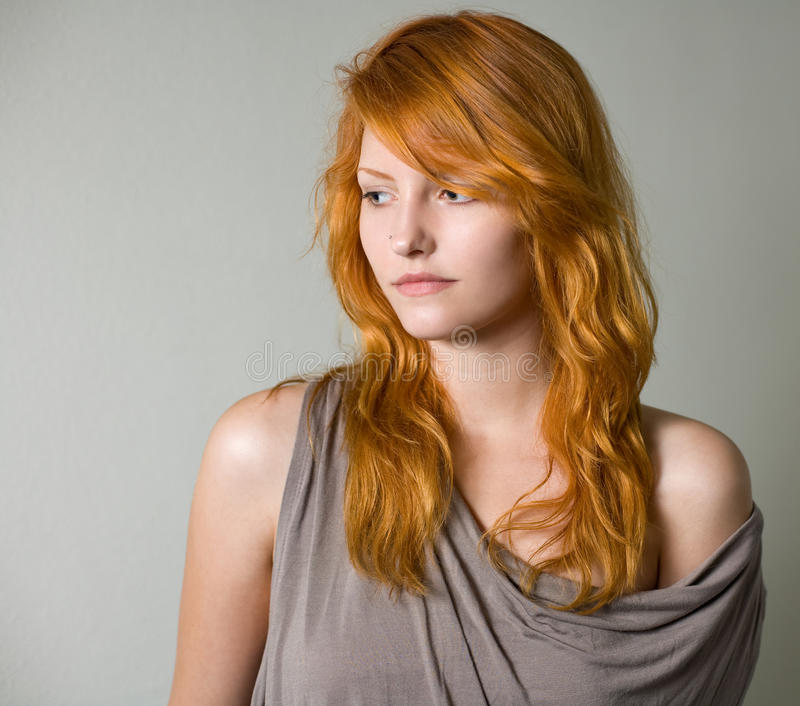 Artistic portrait of gorgeous young redhead. Artistic portrait of gorgeous young redhead wearing gray top royalty free stock images