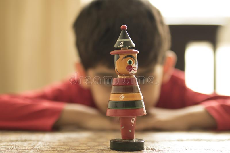 A boy is focused towards a wooden toy. An artistic portrait of a small boy who is staring at a wooden toy. Children are full of dreams and our society`s royalty free stock images