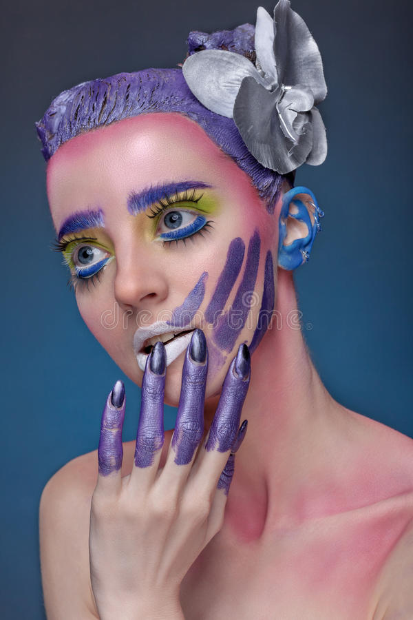 Artistic portrait of woman. Artistic portrait of a woman with bright creative make-up and a flower on her head. Conductive hand over his face stock image