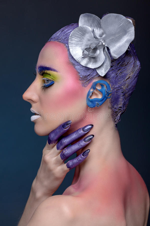 Artistic portrait of woman. Artistic portrait of a woman in half-turn with a hand on his neck. With a creative make-up and a flower on her head stock image