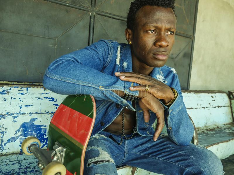 Artistic portrait of young attractive and fit black African American man sitting on corner street bench holding skate board posing. Artistic portrait of young stock photography