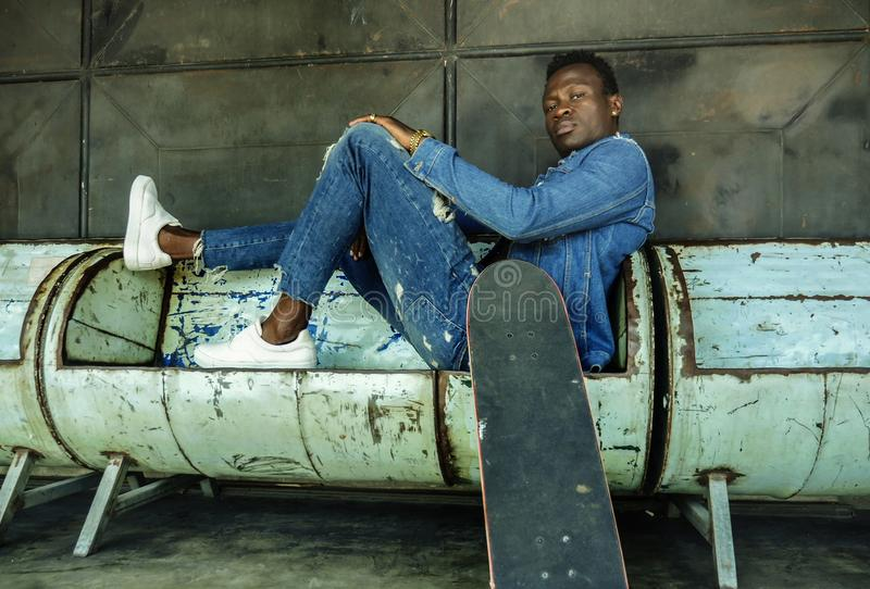 Artistic portrait of young attractive and fit black African American man sitting on corner street bench holding skate board posing. Artistic portrait of young royalty free stock image