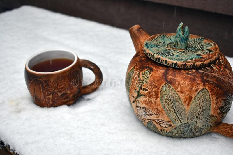 A pottery cup of steaming black tea and a teapot in the falling snow royalty free stock images